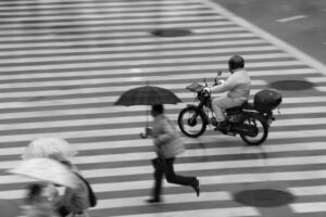 a bit blurry because i was panning with the motorcycle, but i like how it came out in the end, with the crosswalk lines, the man rushing to work in the rain and the motorcycle. (piqs.de ID: 1684c5f71373f3e80dd00a6f91a7945b)